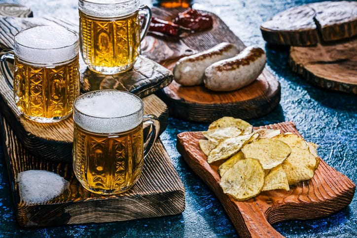 Three crystal mugs of golden beer with grilled bratwurst and homemade potato chips. Spotty blue background. Handmade wooden dishware. Close-up