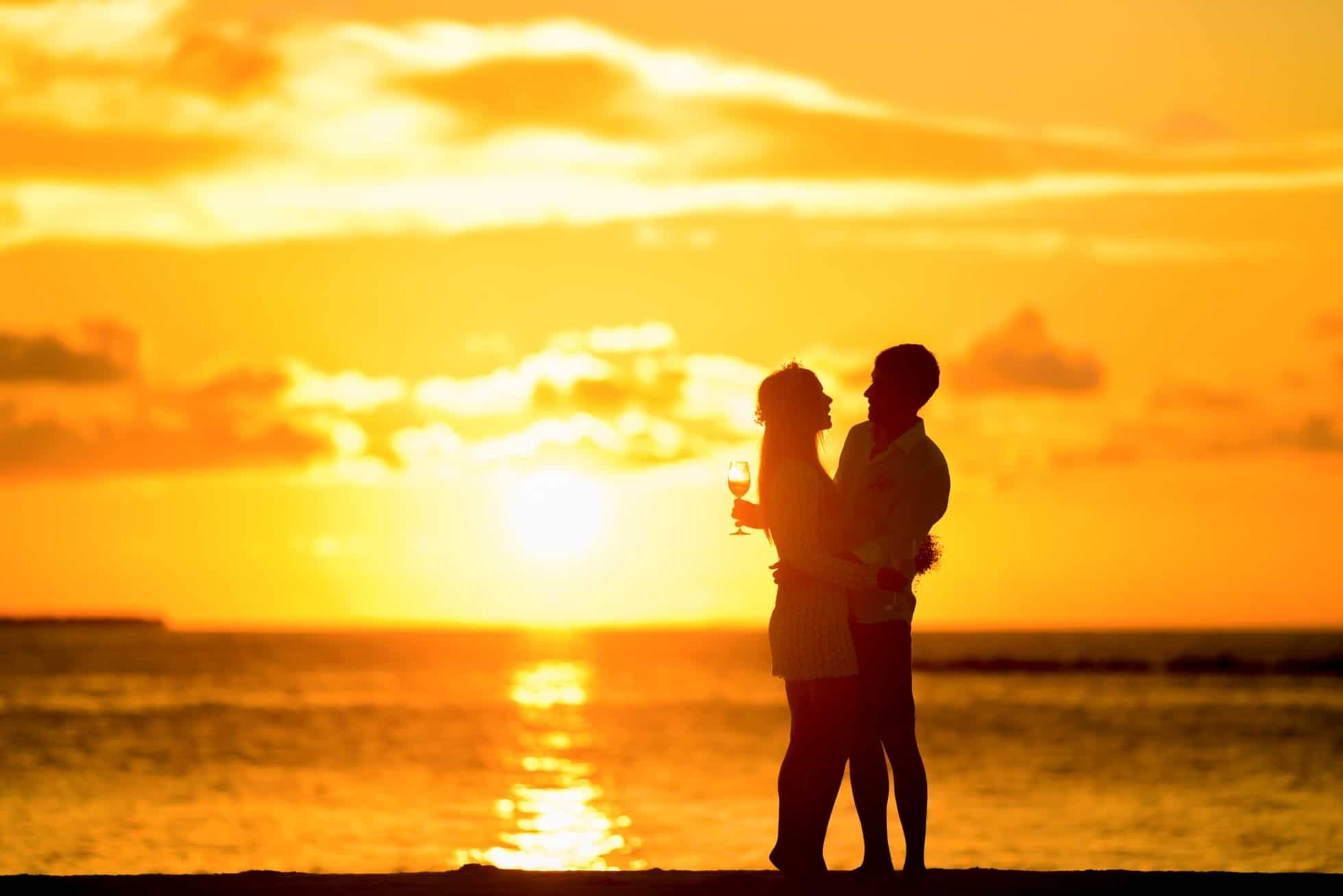 Man Hugging His Wife On The Beach During a Lovely Sunset