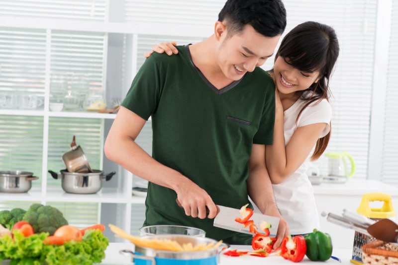Smiling couple spending time together in the kitchen, guy chopping vegetables