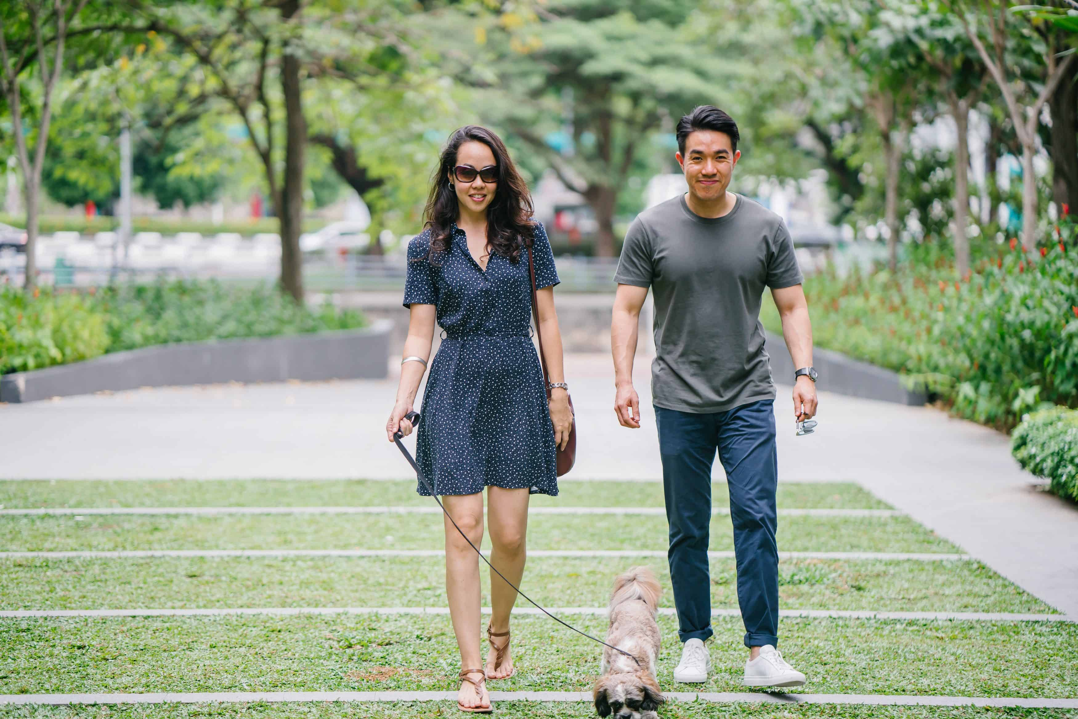 Asian couple on a date walking their pet dog