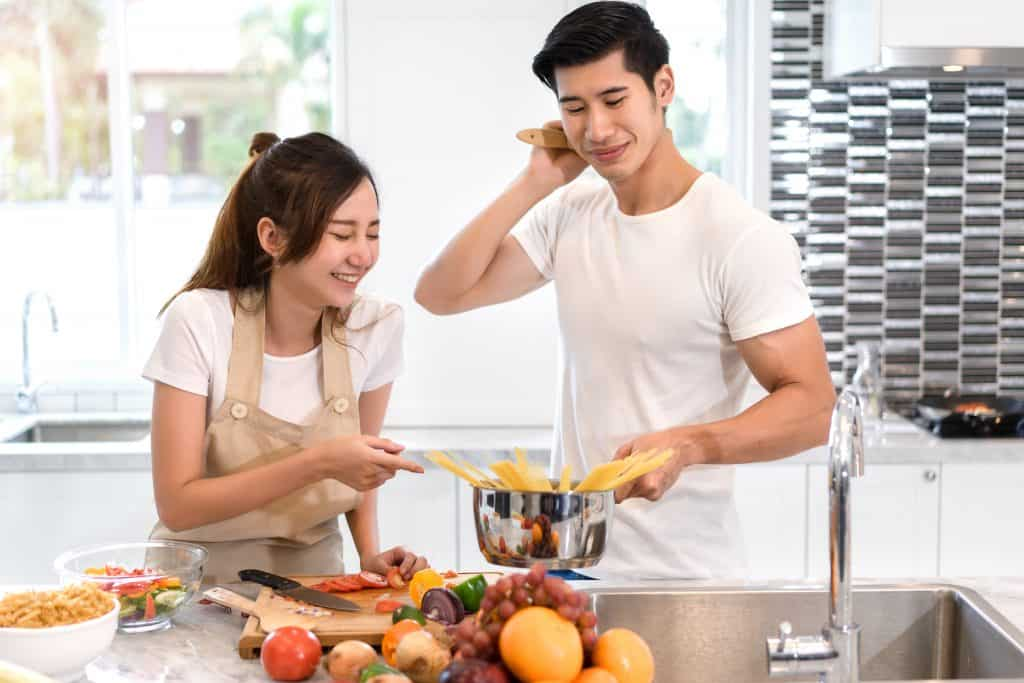Young asian woman cutting slice vegetables making salad healthy food with fruits and man cooking menu for dinner in kitchen at home fun couple together romantic