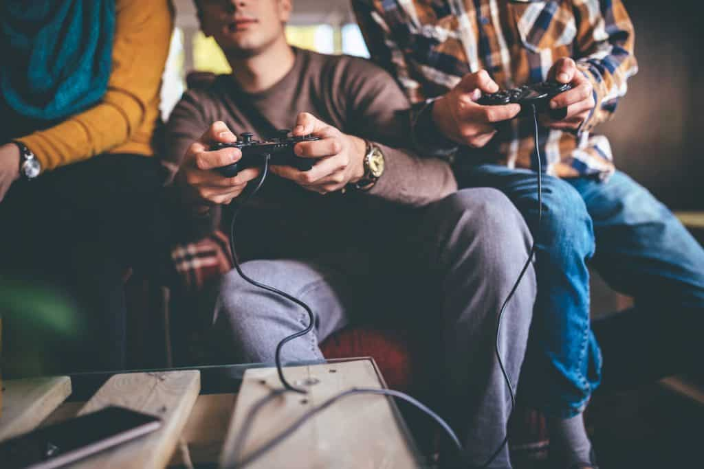 Group of three friends playing video games in office after work