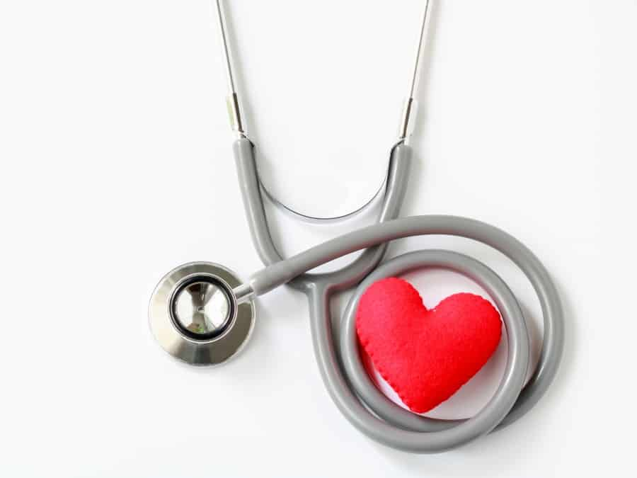 Gray stethoscope with red heart isolated on white background. Medical instruments used to hear sounds within the patient's body. Top view.