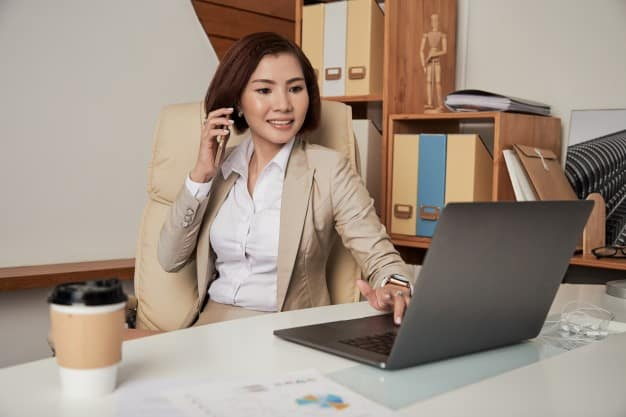 a business woman making a call and using a laptop