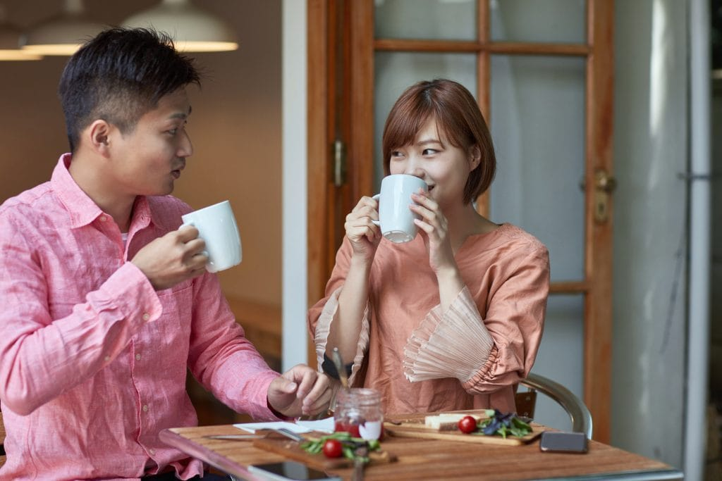 Affectionate man and woman drinking coffee at cafe. Heterosexual couple is looking each other face to face at table. They are in love.