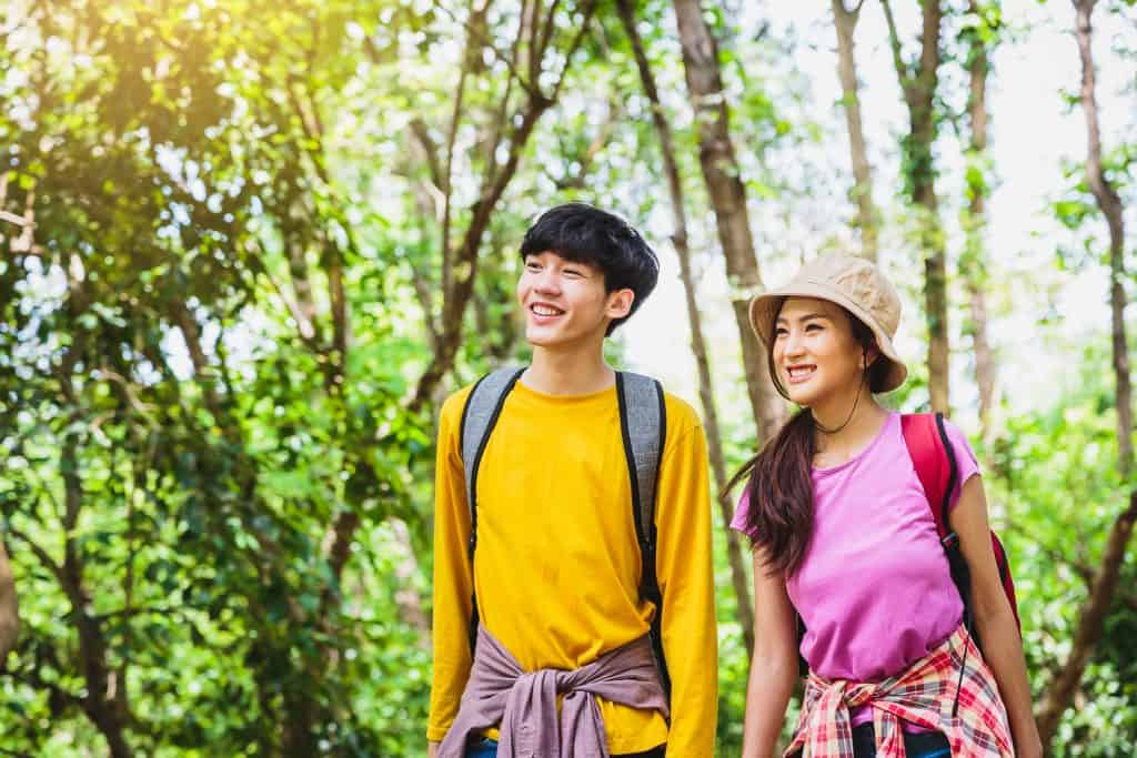 Young Asian couple hikers with backpacks enjoying walking in the forest
