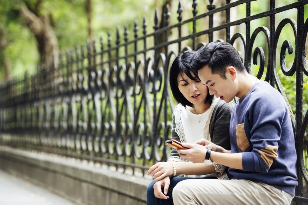 Mid adult couple sitting by railings and checking mobile phone, decisions, text messaging, connections